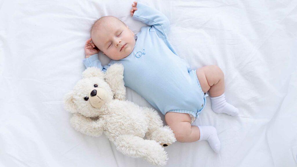 Bebé dormido junto a su osito