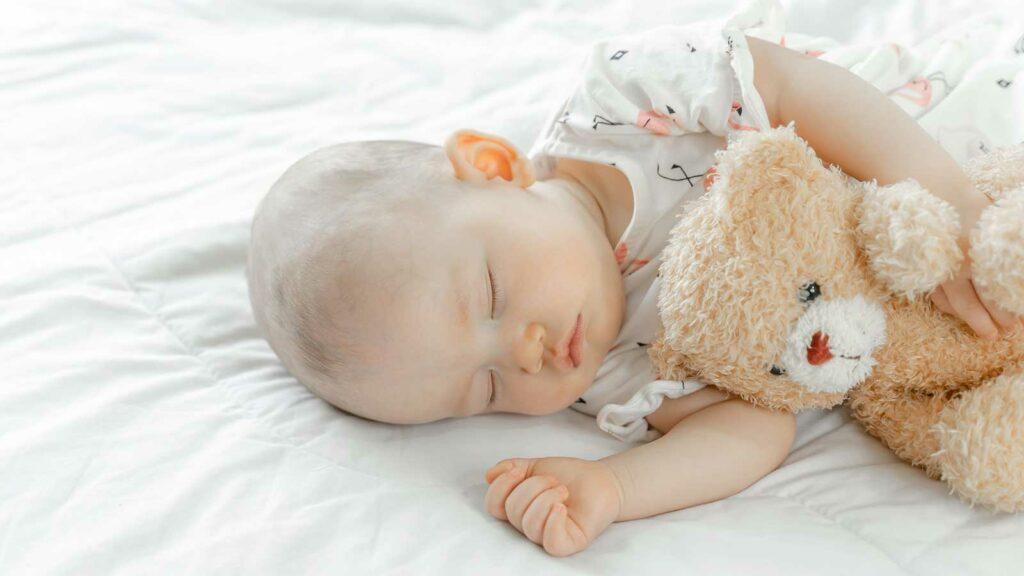 Bebé dormido abrazando a su oso de peluche
